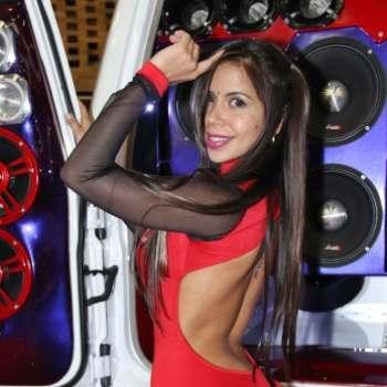Modelo posando junto a un montaje de subwoofers en una competencia de audio